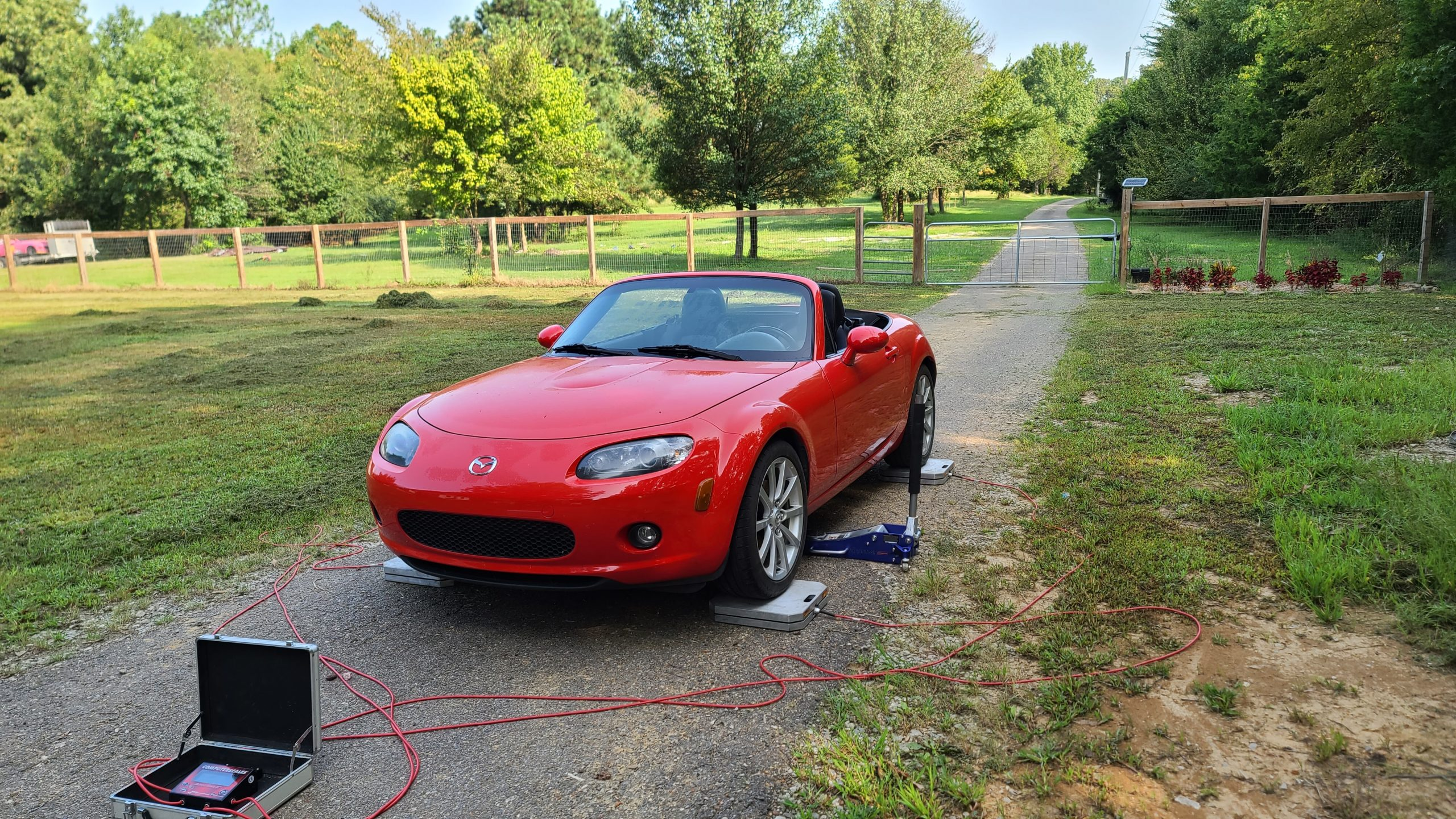 The NC MX-5 on longacre scales to calculate the overall weight of the car without driver and a full tank of gas.